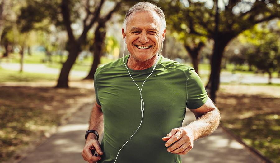 Healthy senior man in fitness wear running in a park