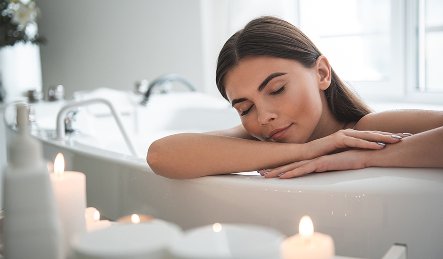 woman enjoying a soak in the bathtub with her favorite self-care products