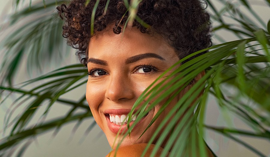 Young woman with curly short hair smiling through leaves