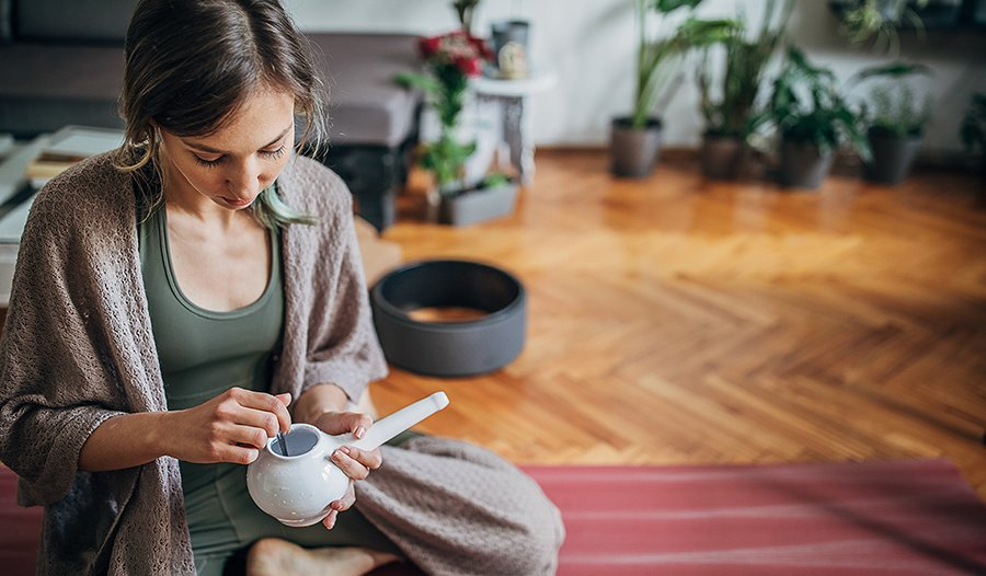 Young woman using neti pot at home after yoga practice
