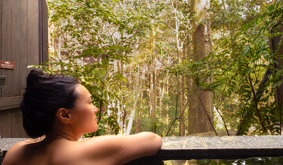 woman participating in self-care in outdoor forest hot spring