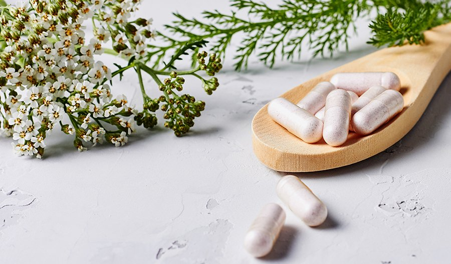 Herbal supplement in capsules and plants over grey background.