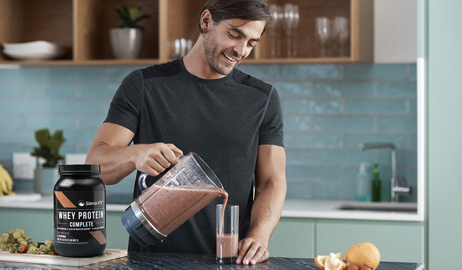 Young athletic male making protein shake in kitchen with whey protein