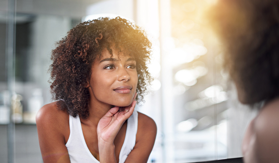 woman looking in the mirror after evening skincare routine as her self-care