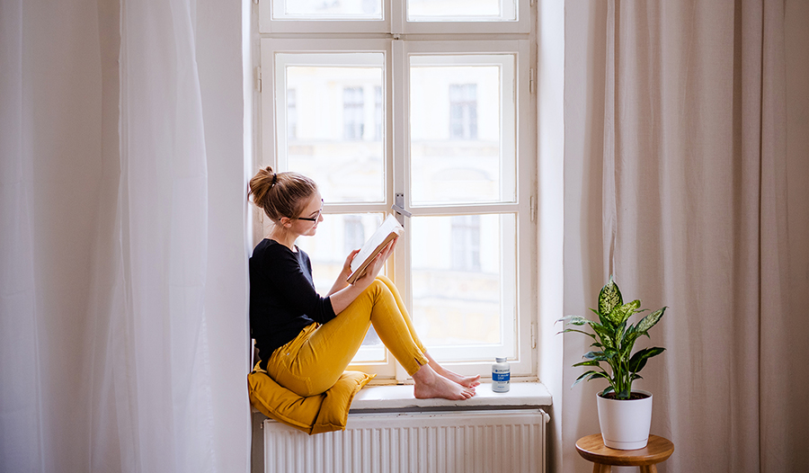 Young woman sitting in window sill reading a book