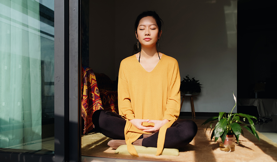 Peaceful Asian woman sitting in the sun meditating