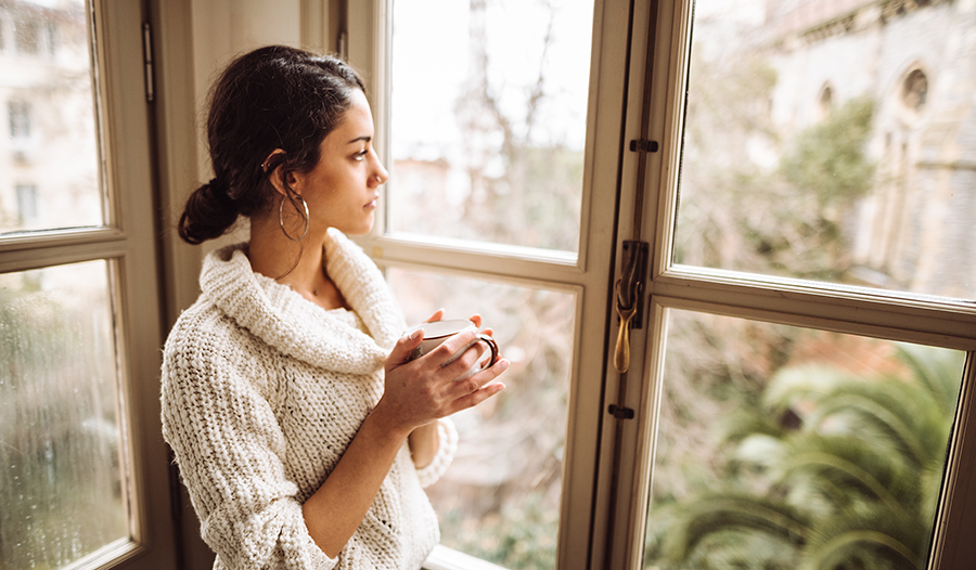 Young woman in sweater holding a cup of tea looks out the window