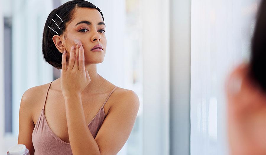woman applying lightweight summer moisturizer to her skin