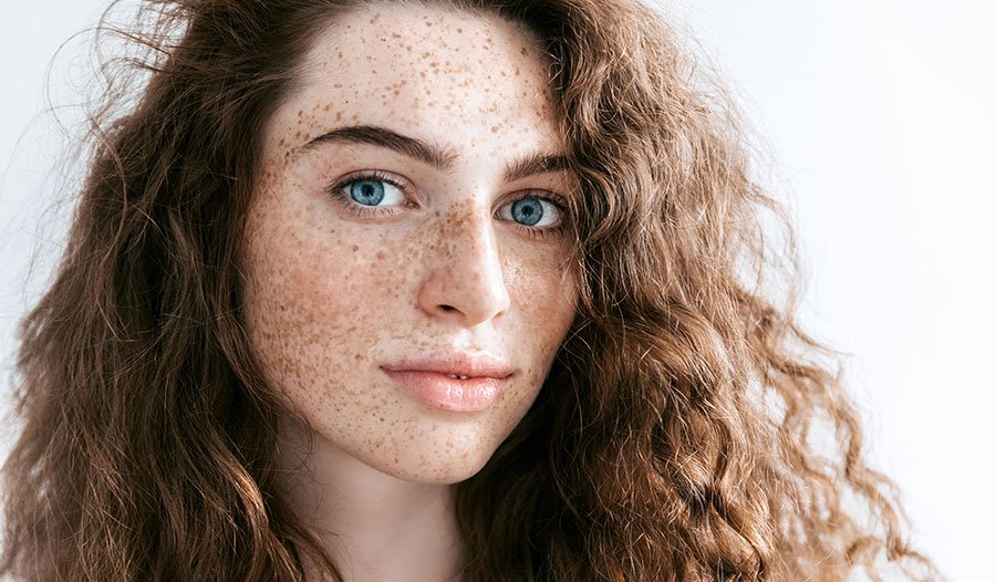 young woman with blue eyes and freckles thinking about her summer skincare routine