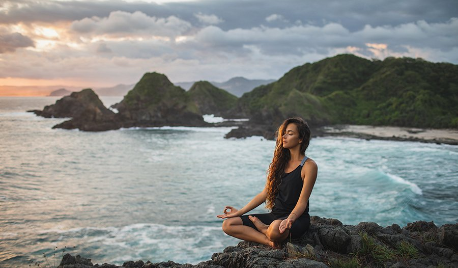 Woman practicing yoga sitting in lotus pose at sunset with on the coast with mountain view.