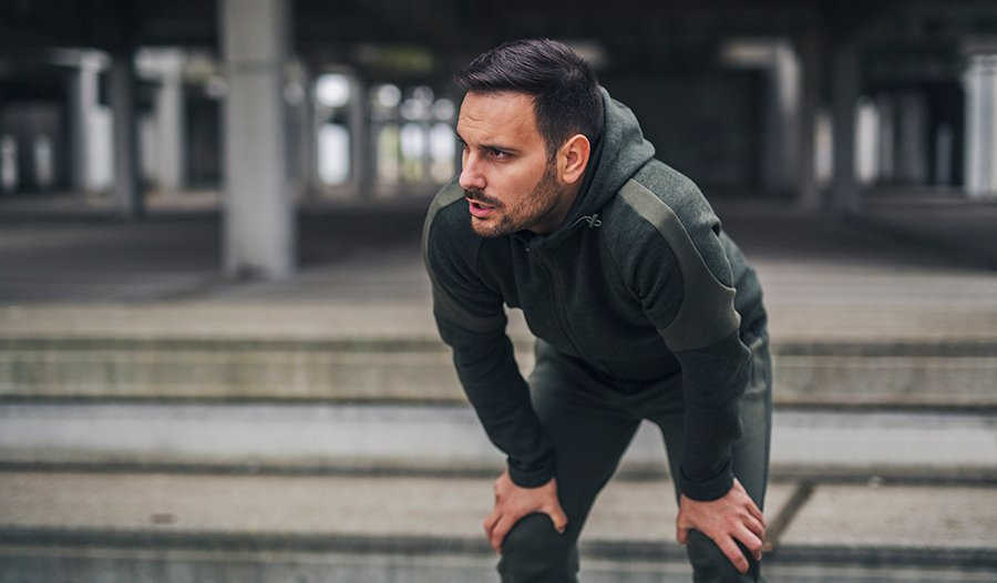 Brunette man in workout clothes catching his breath