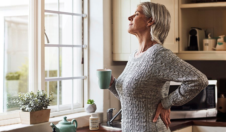 Woman standing near kitchen window with mug in her hand