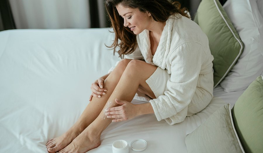Young brunette woman in bath robe sitting on bed applying body butter