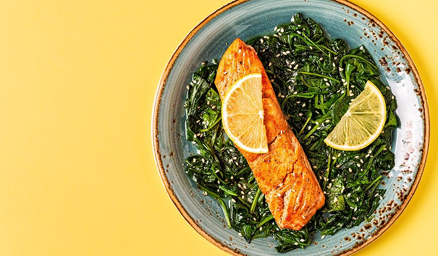 Grilled salmon with lemon on spinach on yellow table.