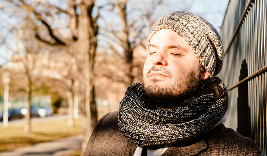Young male with beard wearing a hat and scarf taking a deep breath