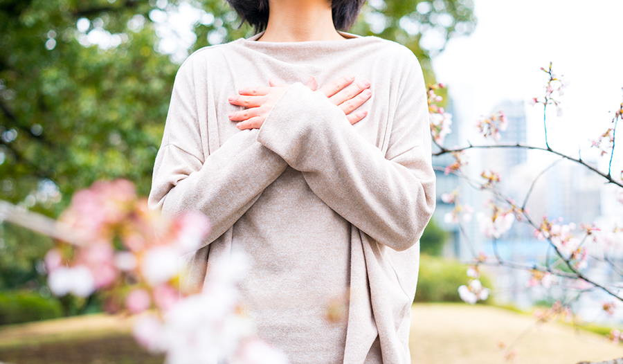Woman surrounded by cherry blossoms with hands over heart