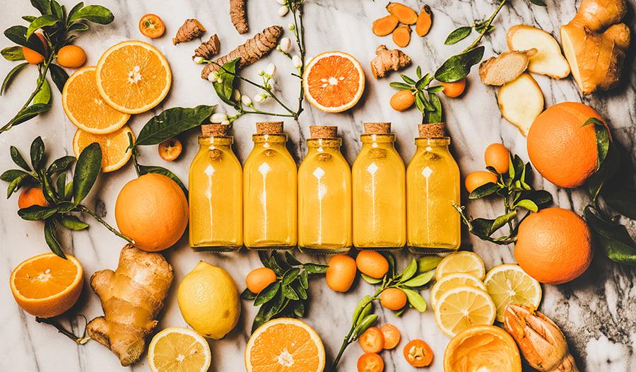 Healthy turmeric ginger lemon immune shots on marble surface