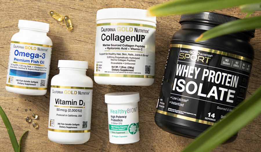 Flat lay of supplements on table with palm plant including omega-3 fish oil, vitamin D, collagen, pr