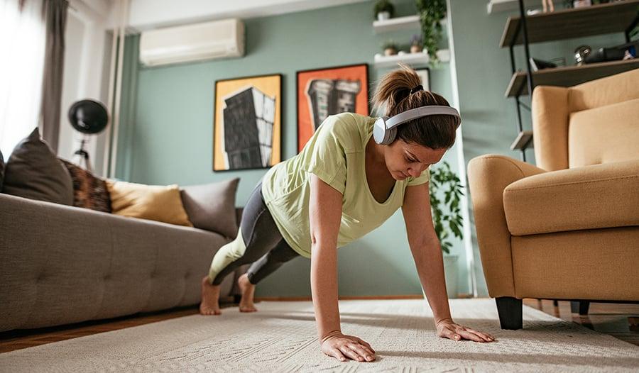 Woman wearing headphones exercising at home