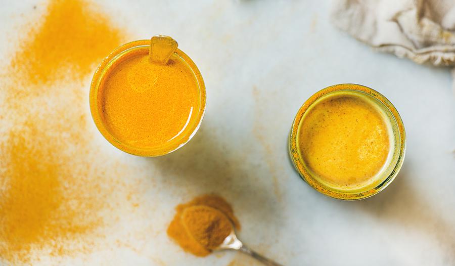 Glasses of golden turmeric milk on white table