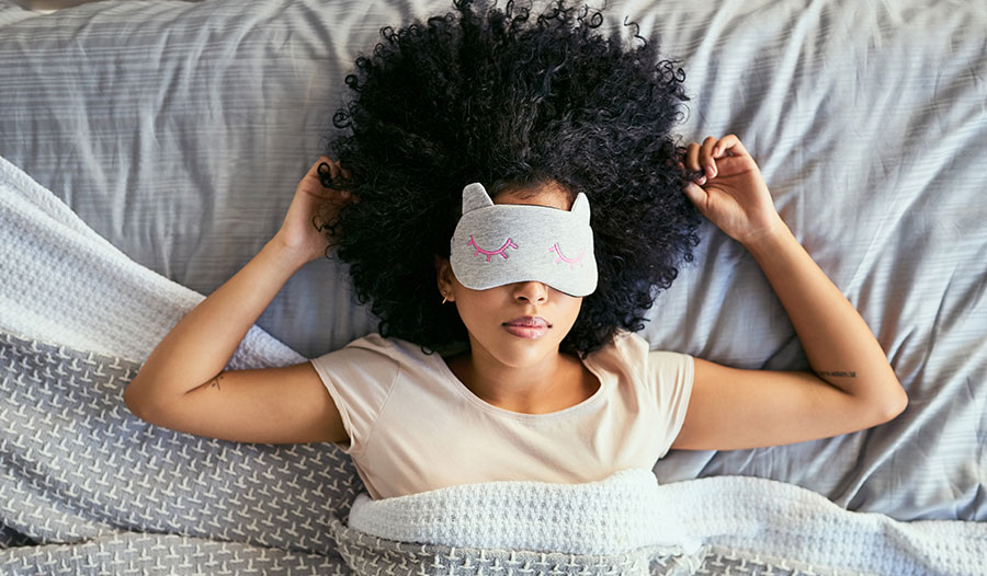 woman lying in bed with an eye mask over her eyes for self-care