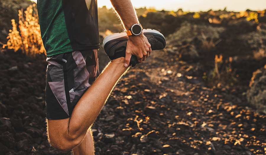 Male runner stretching leg preparing for run outdoors.