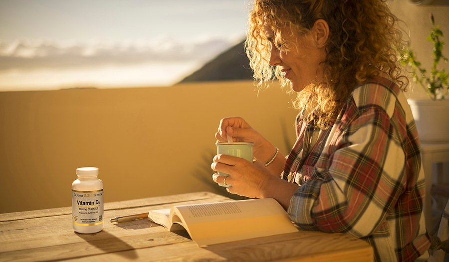 Woman sitting outside on her deck with coffee, a book, and vitamin D bottle