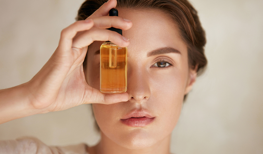 woman holding up a vitamin serum to her eye and looking through the glass bottle