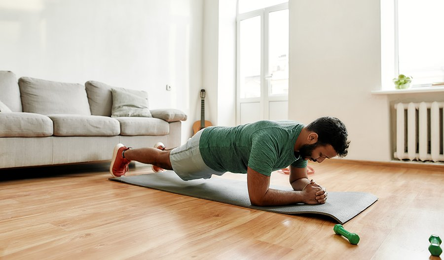 Male exercising in his living room doing a plank on a workout mat