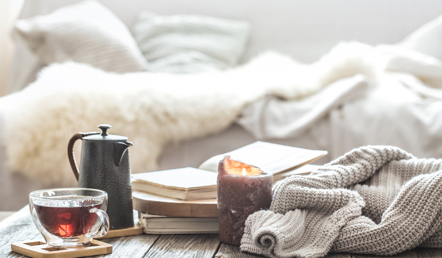 self-care items of tea, tea cup, and candle with a couch and comfortable blankets