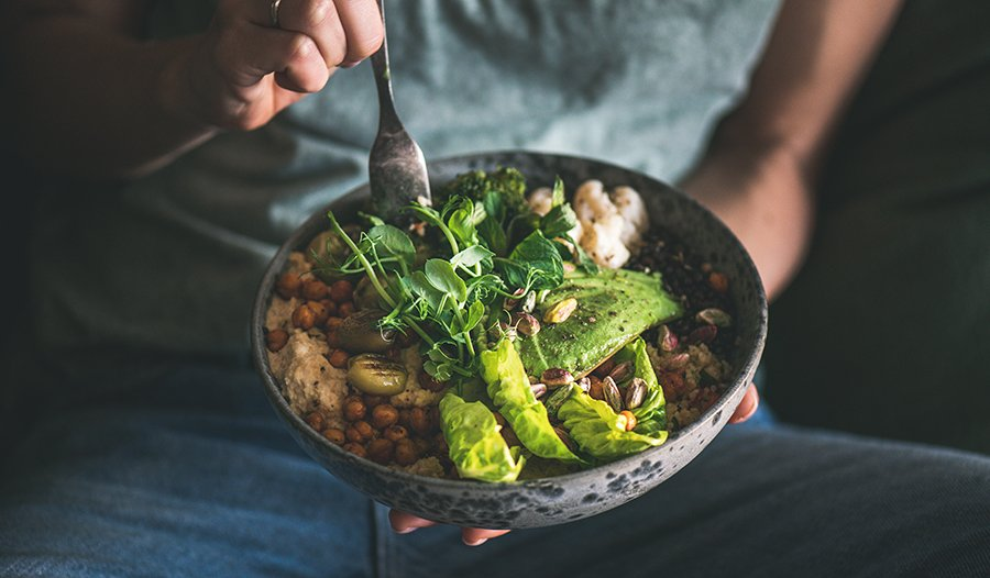 Woman in t-shirt and jeans eating vegan bowl for lunch or dinner with avocado and veggies