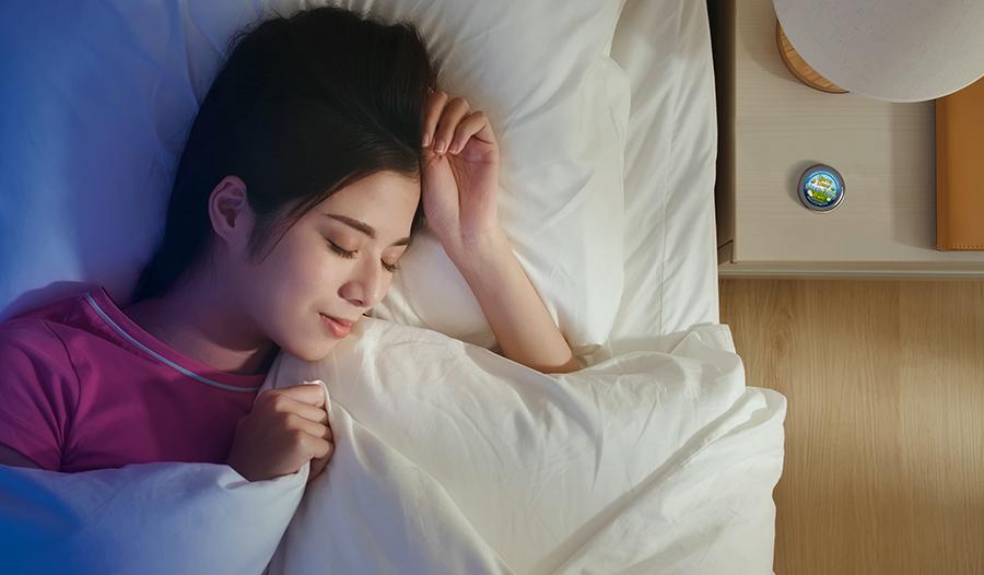 Asian woman asleep in bed with sleep balm on nightstand