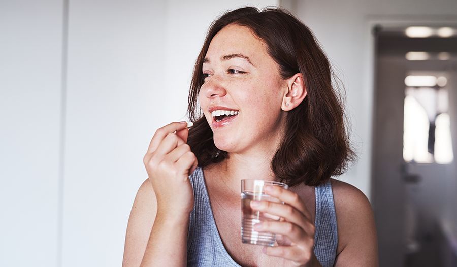 Healthy young woman with glass of water taking vitamin