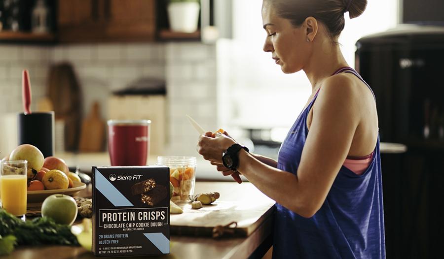 Женщина готовит на кухне смузи со свежими фруктами и протеиновыми добавками